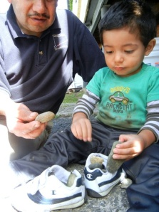 """""""How many rocks can fit in this shoe?"""" This toddler is becoming familiar with shapes and spatial relationships as he puzzles out the arrangement of stones. With help from his caregiver, Juan, he also may be learning comparison words like """"more"""" and """"less"""" or """"bigger"""" and """"smaller."""""""