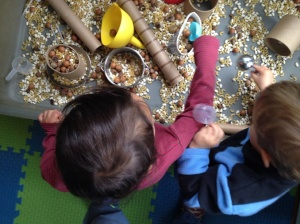 These children have cereal, acorns, and beans to experiment with.
