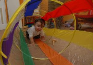 """As infants and toddler use their bodies to explore, they can be introduced to words like """"over,"""" """"under"""" """"on top"""" and """"below""""—all vocabulary that will help them make sense of spatial relationships."""