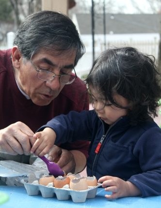 Alejandro Reyes guides a child planting a seed in an eggshell.